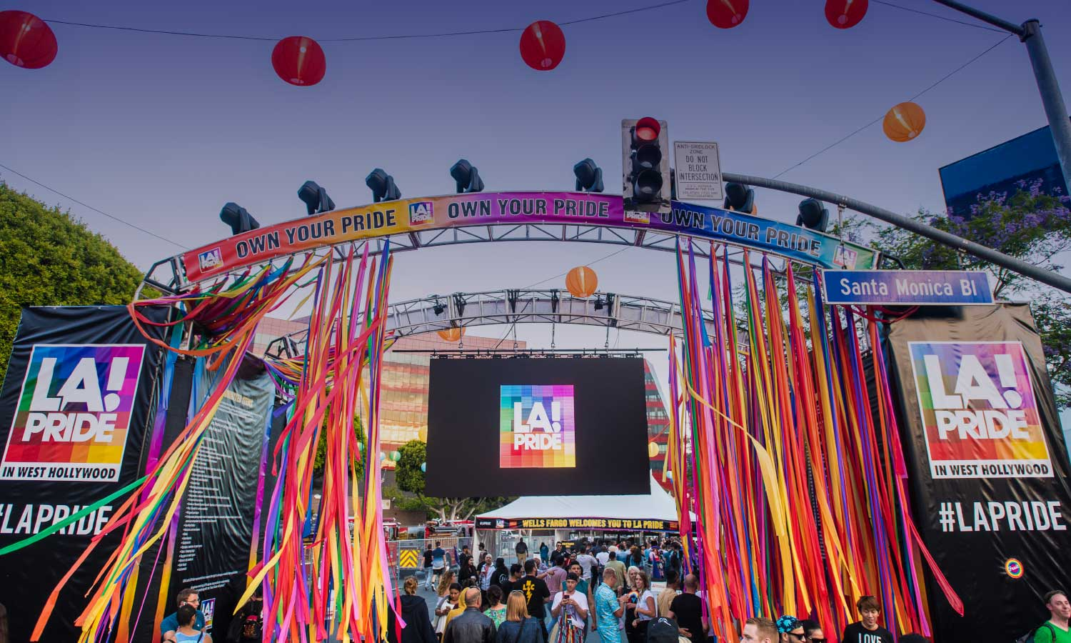 An archway of colorful streamers and Chinese lanterns at LA's Pride Parade with people underneath the arch