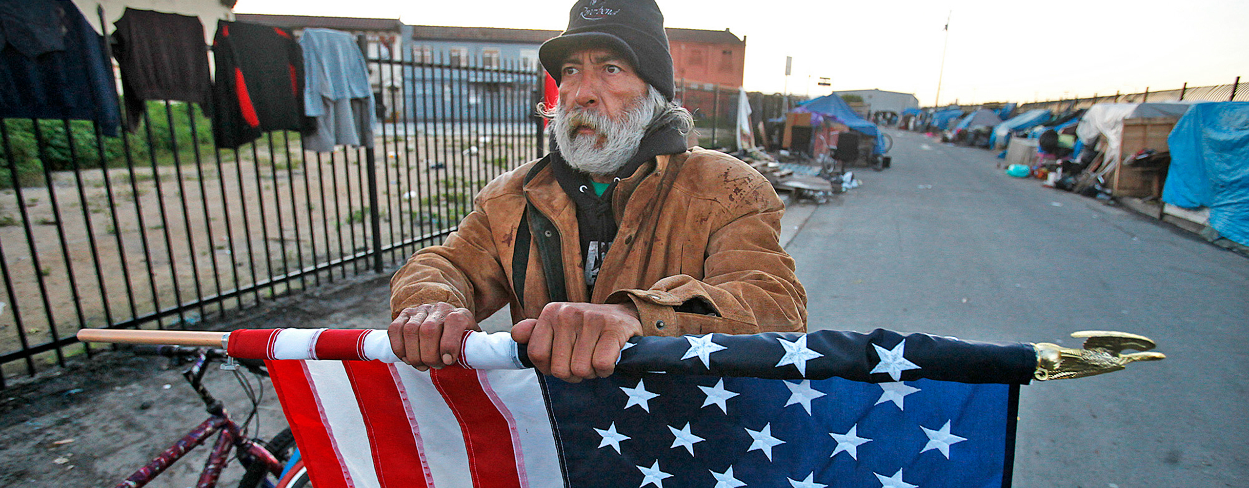 A homeless person holds a slightly rolled American flag. They appear to be standing in Skid Row Los Angeles, a street with many homeless tents lining the street. There is a fence with clothes hanging on it to the left of the homeless man, as well as two bikes to his direct left.