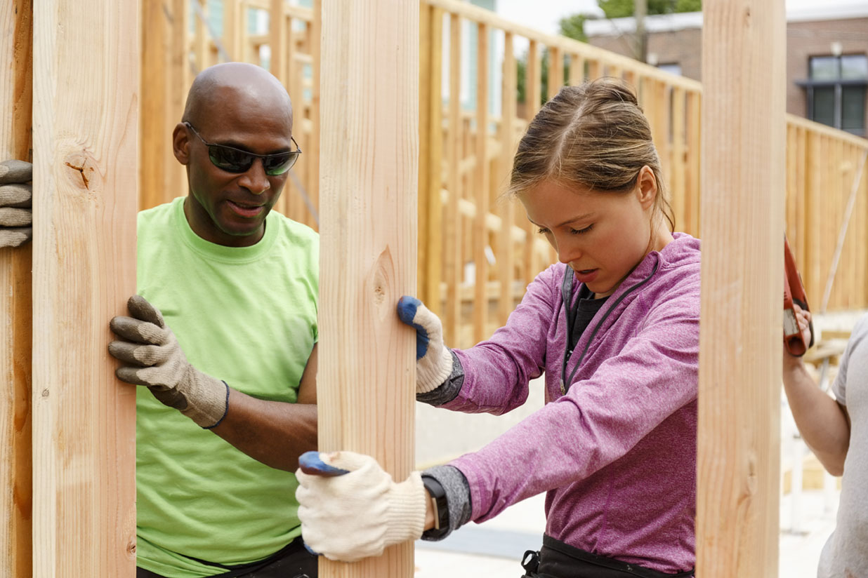 Two people are building a wall together. A women in a pink sweater with gloves on is holding a piece of wood upright. An African American man in a lime green shirt is to her left on the next piece of wood, also holding the wood upright with his gloved hands. He is wearing dark sunglasses. There is a hand to the right of the screen holding a saw.